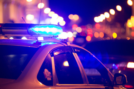 ambulance car: Blue light flasher atop of a police car. City lights on the background. Stock Photo
