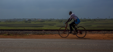 country roads: Beach Road, Accra, Ghana, West Africa - July 28, 2014: Local resident riding the bicycle along the road from Tema to Accra Editorial