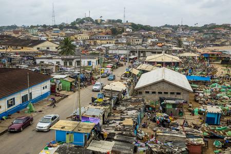 ケープコースト、ガーナ、西アフリカ - 2014 年 7 月 31 日: 岬海岸の中央地区の表示します。小屋と通り、ヤードでいくつかの漁船に沿って屋台があり 報道画像