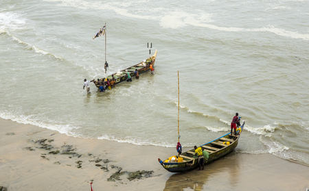 locals: Cape Coast, Ghana, West Africa - July 31, 2014: Fishermen after fishing. The main occupation of locals in this area is fishing. Photo was taken from the Cape Coast Castle