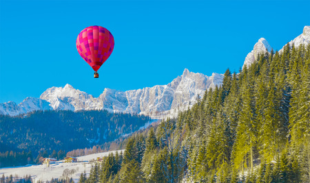 Sunny winter mountain landscape with a purple air balloon in the sky