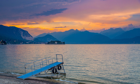 View of summer sunset over the Maggiore Lake in Stresa, Italy. There is the boat ladder in the foreground. Stok Fotoğraf