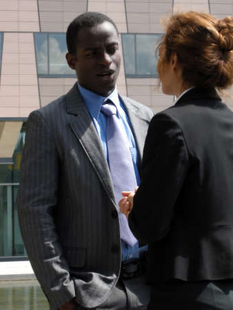 Businessman and businesswoman negotiate in the open air photo