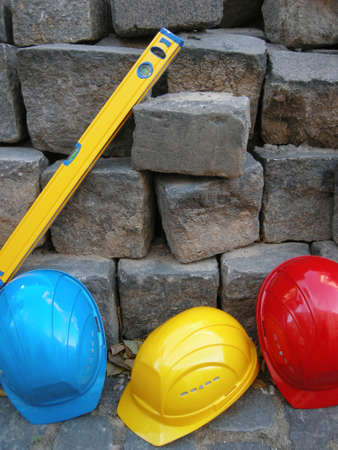 Construction Still life - Level, yellow, blue and red helmet infront of stones photo