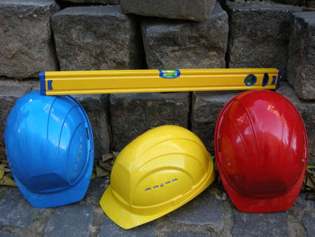 Break from work on building site - Level, yellow, blue and red helmet before Cairn photo