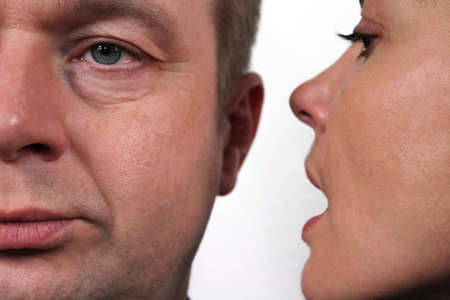 hears: Secret whisper - the woman whispered to the man a secret in his ear Stock Photo