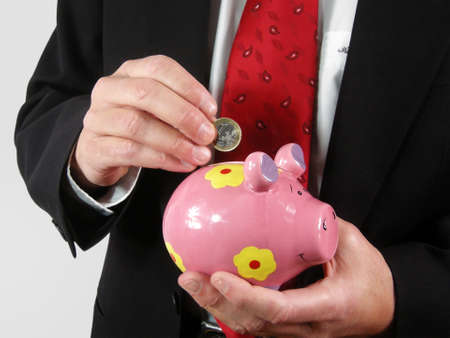 Save - the man put a coin into the piggy bank Stock Photo - 8954743