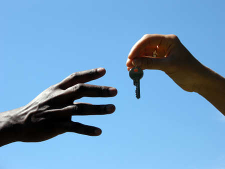 key handover: Handover - extends a hand to the other a key Stock Photo