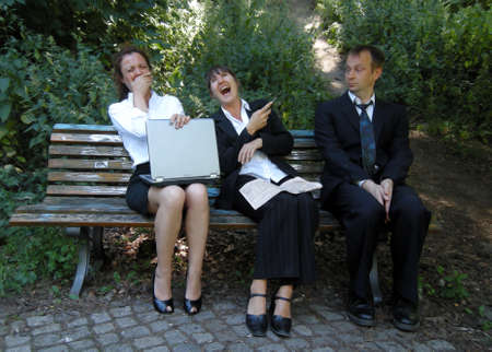 Businesswomen have fun - Businesswomen laughing at the man photo