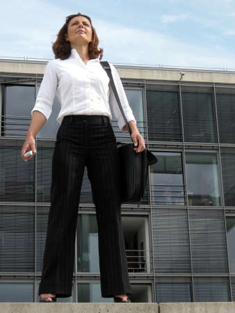 motivating: Motivated career woman in front of her office