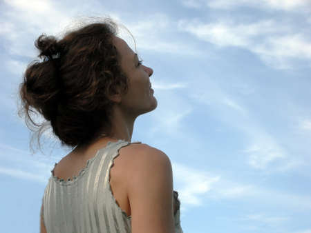 Woman looks longingly to the sky