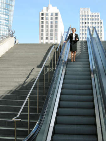 Businesswoman on escalator photo