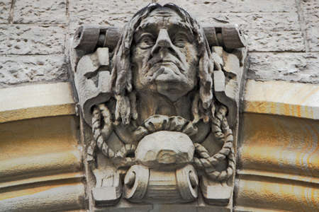 heads old building facade: Statue on the City Hall Dessau Stock Photo