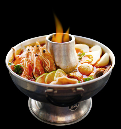 Thai Spicy herbal soup (Tom Yum) served in hot pot on fire