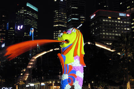 3d lion: Singapore, June 17 2015 - Merlion in colorful from laser with building in background