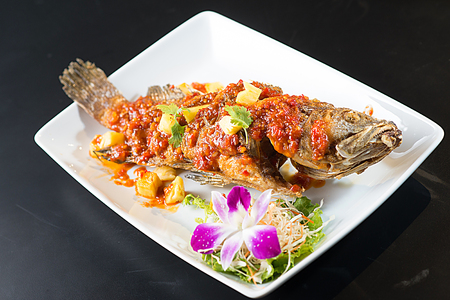 Thai Tradition Food: deep-fried fish topped with fresh herbs and sweet spicy sauce on plate