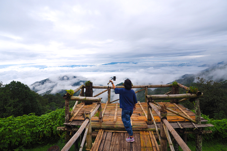 Fog and cloud viewpoint mountain with a girl taking photo at Chiangmai, Thailand Stock Photo