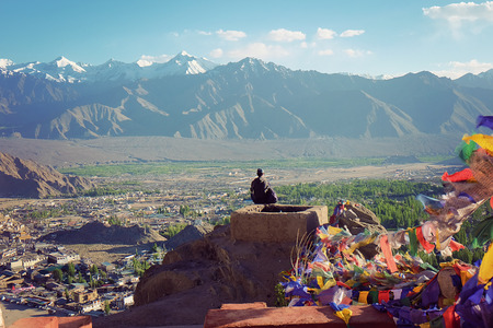 India - June 18, 2017: People sit on top of monastry with mantra flag beside to viewing mountain in Leh Ladakh, India Editorial