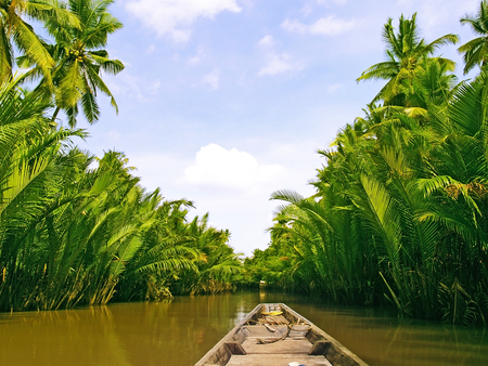 local traditional long tail boat cruise on tropical river in thailand
