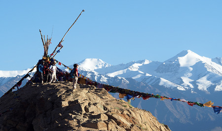 Happy unidentified tourists stand on top of the mountain with mantra flags at Namgyal Gompa in Leh, India