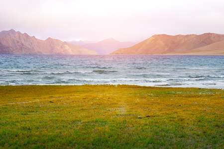 Colors of Pangong Lake, scenic view of Pangong Tso against the background of distant mountain range and cloudy blue sky with green field, Ladakh Foto de archivo