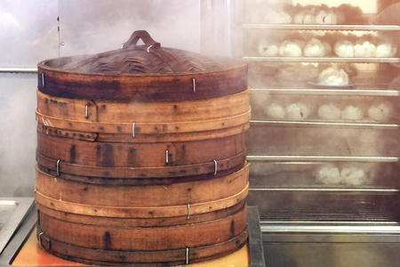 Large bamboo Basket Steamer on fire to cooked Dim Sum dumplings at chinese asian local restaurant Banco de Imagens