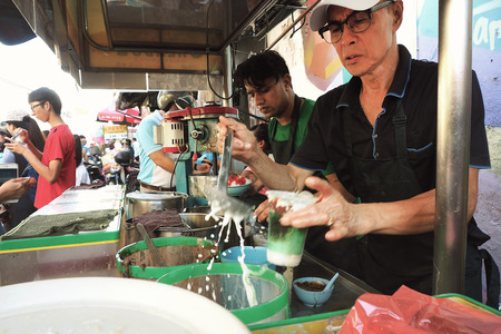 Malaysia - AUGUST 17 2017: Famous Teochew Chendul stall with staff doing a takeaway glass of chendul, Georgetown Penang Malaysia, movement blurred photography