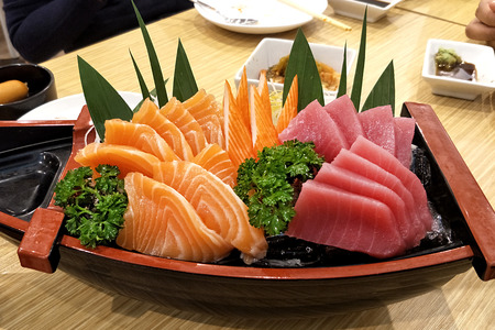 Japanese food - Sashimi Salmon and tuna served on boat in Japanese restaurant environment