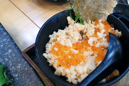 Japanese style food Salmon fried rice topped with salmons egg and deep fried salmons skin served on black ceramic bowl in local restaurant