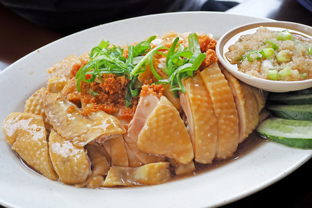 Asian food - Chinese Steamed chicken cut in piece served on white dish with tiny bowl of ginger garlic dip Banco de Imagens