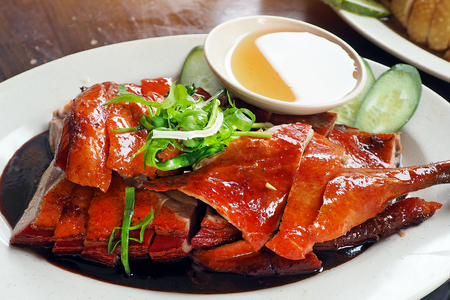 Chinese Roasted duck cutted and served on white dish topped with black gravy herbal sauce