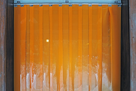 orange color Industrial warehouse plastic PVC strip curtains hanging at the wood door