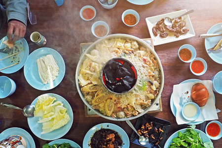 family enjoy eating traditional local asian chinese yunnan style grand hotpot on table center - photo take from top above view