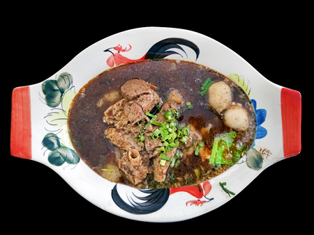 local thai noodle with herbal and pork blood thick soup called Kuay Teow Rua served in common thai style bowl isolated on black background