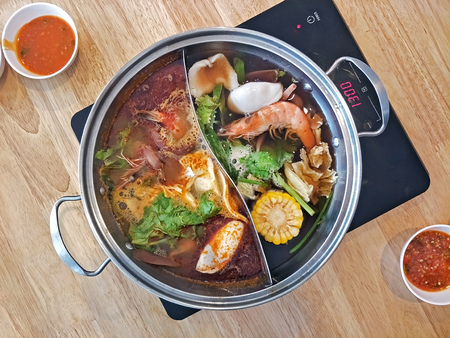 japanese hot pot shabu with double side pot with spicy and soya black soup separate on each side on induction stove 스톡 콘텐츠