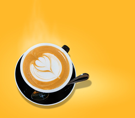 isolated on yellow background  of cup of coffee hot smoke latte art in heart shape served on black modern vintage cup