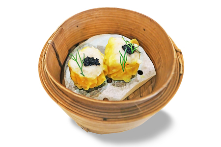 Traditional Chinese Food Dim Sum - Pork and prawn mixed dumpling steamed served on bamboo basket topped with black caviar Foto de archivo