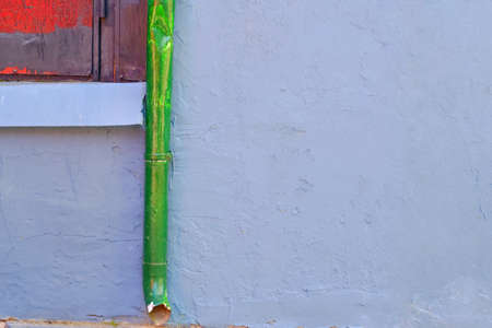 Green water pipeline on concrete ceiling outside building.