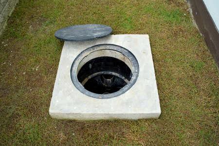 Un agujero de trampa de grasa con el sistema de drenaje alrededor de la casa. Foto de archivo