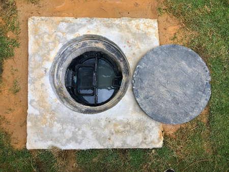 Un agujero del tanque subterráneo de trampa de grasa con el sistema de drenaje alrededor de la casa.