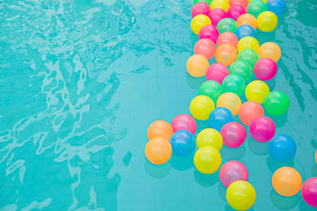Small colorful beach balls floating in swimming pool abstract concept for pool party and summer vacations.