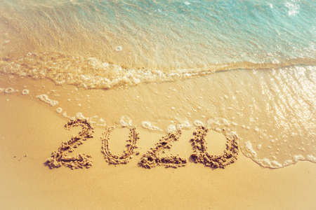 Happy New Year 2020 concept, 2020 number lettering on the sea beach, wave and golden light of sunset. Imagens