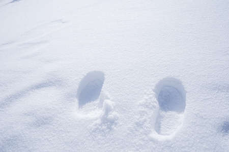 The picture of footprints or foot step on the snow. Standard-Bild - 126640428