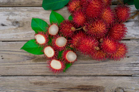 Fresh rambutan on the wood table background. Top view with copy space. Stock fotó
