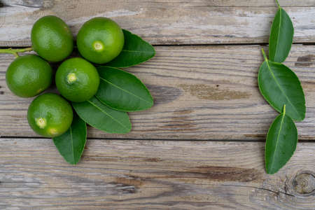 Fresh limes or green lemons on wood table background. Top view with copy space Stock fotó