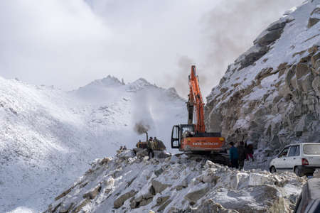 27 October 2018, Khardung La Rd, Jammu, and Kashmir, India. Workers and Backhoe destroy the rock stone and snow which block the roadway in the mountain. Stock fotó