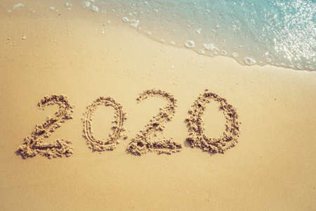 Happy New Year 2020 concept, 2020 number lettering on the sea beach, wave and golden light of sunset. Stock fotó
