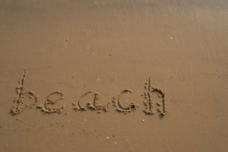 Vacation on the sand beach concept. Beach words written into the sand on the beach at Rayong, Thailand.