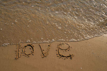 Love and Valentine concept. Love words written into the sand on the beach at Rayong, Thailand