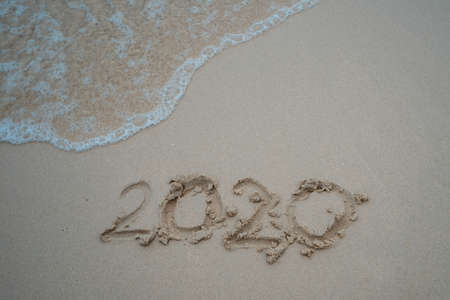 Happy New Year 2020 concept, 2020 number lettering on the sea beach, wave and golden light of sunset. Stock fotó - 137945461